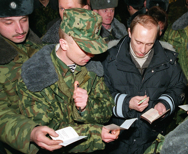 Vladimir Putin signs autographs for Russian soldiers in Gudermes, east of Grozny, during the conflict in Chechnya, January 1, 2000. (Photo by Reuters)