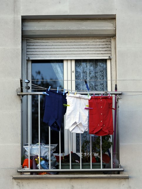Blue, white and red shirts, the colours of the French national flag, hang from a balcony in Marseille, France, November 27, 2015 as the French President called on all French citizens to hang the tricolour national flag from their windows on Friday to pay tribute to the victims of the Paris attacks during a national day of homage. (Photo by Jean-Paul Pelissier/Reuters)