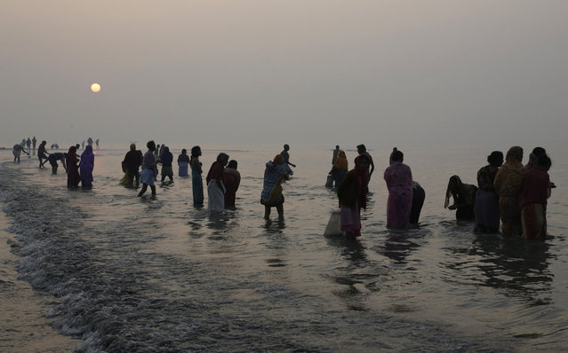 Hindu pilgrims take holy dips to mark Makar Sankranti festival in Gangasagar, India, Thursday, January 15, 2015. (Photo by Bikas Das/AP Photo)