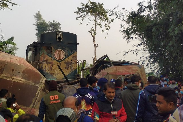 Onlookers gather at the site of an accident after a train rammed into a passenger bus in Bangladesh's northern border town of Joypurhat on December 19, 2020. (Photo by AFP Photo/Stringer)