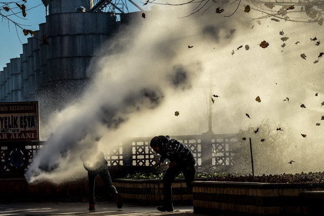 Turkish riot police use water cannon to disperse protestors from Diyarbakir's historical Sur district which has been placed under a curfew, on December 6, 2015 in Diyarbakir. More than a week after prominent Kurdish lawyer Tahir Elci was killed in broad daylight in a street in southeastern Turkey's main city, the Turkish authorities appear no closer to solving the crime amid bitter recriminations over who was to blame. (Photo by Ilyas Akengin/AFP Photo)