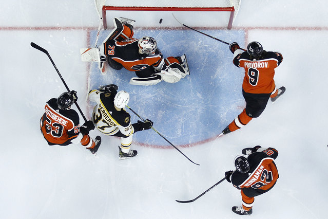 Philadelphia Flyers' Carter Hart (79) and Ivan Provorov (9) cannot stop a goal by Boston Bruins' David Pastrnak as Connor Bunnaman (82), Shayne Gostisbehere and Patrice Bergeron (37) look on during the first period of an NHL hockey game, Wednesday, February 3, 2021, in Philadelphia. (Photo by Matt Slocum/AP Photo)