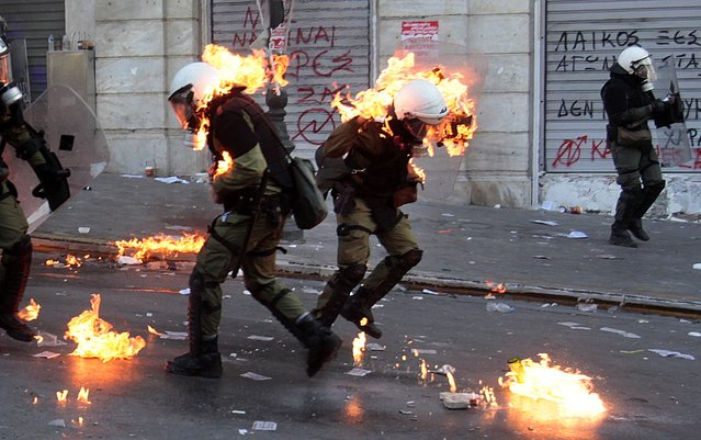 Policemen are set ablaze on fire by a petrol bomb thrown by protesters during clashes near the Parliament building in Syntagma (Constitution) square in Athens in this October 20, 2011 file photo. (Photo by Yannis Behrakis/Reuters)