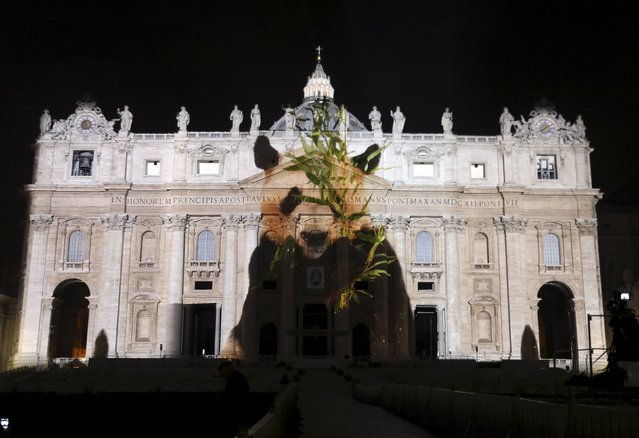"""A picture of a panda, part of an art projection featuring images of humanity and climate change artistically rendered by Obscura Digital, is projected onto the facade of St. Peter's Basilica, as part of an installation entitled """"Fiat Lux: Illuminating our Common Home"""" as a gift to Pope Francis on the opening day of the Extraordinary Jubilee, at the Vatican, December 8, 2015. (Photo by Stefano Rellandini/Reuters)"""