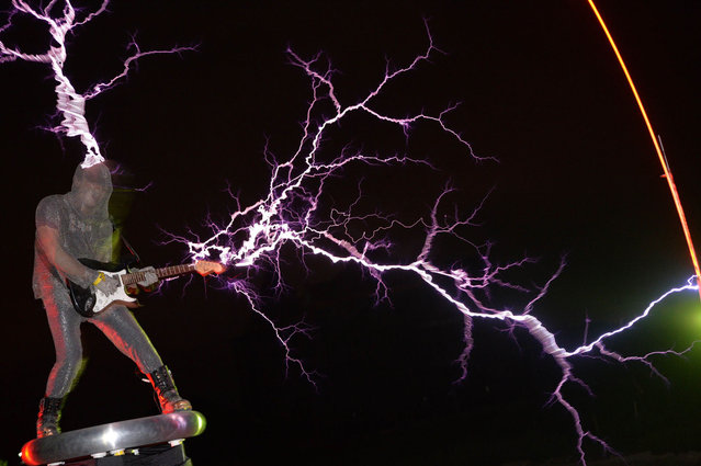"""The guitarist of the band """"Lightningfan"""" Wang Hongbin (L) creates lightning with a Tesla Coil in their village outside of Fuzhou in China's Fujian province on June 24, 2013. The Tesla Coil invented by Nikola Tesla in 1891 is a transformer that produces vast amounts of voltage at high frequencies that creates long bolts of electricity like lightening. Inventor and founding member of the band Wang Zengxiang, an electrical engineer made his first Tesla Coil in 2007 and afterwards formed his 10 member band who, whilst wearing ferroalloy metal suits play guitars, violins and drums with bolts of lightening crackling from them and their instruments to the beat. (Photo by Peter Parks/AFP Photo)"""