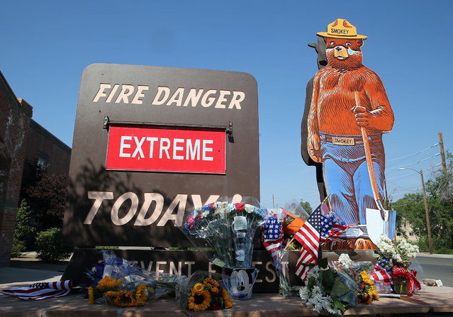"""American flags and flowers adorn a """"Extreme"""" fire danger warning outside of Firestation 1 on July 2, 2013 in Prescott, Arizona. Nineteen Granite Mountain Interagency Hotshot Crew firefighters based out of Station 7 died battling a fast-moving wildfire near Yarnell, AZ on Sunday. Station 7 has been the home of the Granite Mountain Interagency Hotshot Crew since 2010. GMIHC is a national resource that responds to wildland and all risk incidents in the Prescott Basin. (Photo by Christian Petersen/Getty Images)"""
