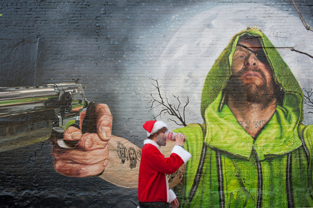 A man dressed as a Santa walks past a mural in Williamsburg during the annual SantaCon pub crawl December 12, 2015 in the Brooklyn borough of New York City. (Photo by Stephanie Keith/Getty Images)