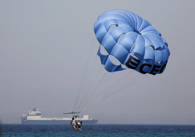 Holidaymakers parasail as a cargo ship crosses the Gulf of Suez towards the Red Sea at El Sokhna beach in Suez, 127 kilometers (79 miles) east of Cairo, Egypt, Thursday, July 19, 2018. (Photo by Amr Nabil/AP Photo)