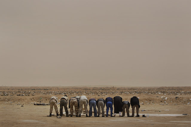 Libyan rebel fighters pray in the desert on hearing claims from other rebels that an airstrike further up the road towards Brega had hit rebel forces killing at least two and injuring more than a dozen, at the west gate of Ajdabiya, Libya, Thursday, April 7, 2011. (Photo by Ben Curtis/AP Photo)