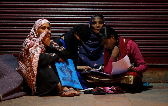 A family checks their documents as they sit outside a bank in the early hours to exchange their old high-denomination banknotes, in the old quarters of Delhi, India, November 16, 2016. (Photo by Adnan Abidi/Reuters)