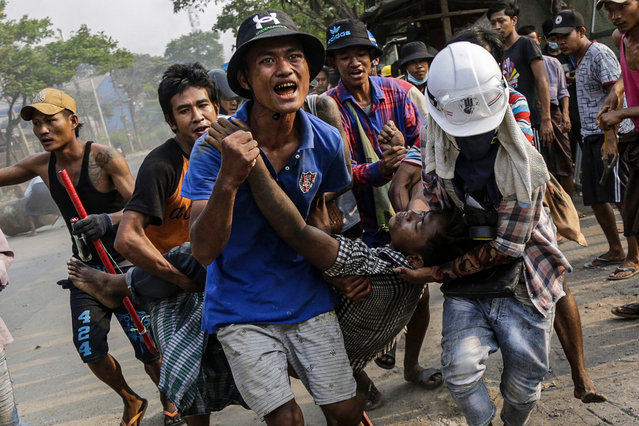 An injured demonstrator is carried to receive medical attention during a protest against the military coup in Hlaingthaya (Hlaing Tharyar) Township, outskirts of Yangon, Myanmar, 14 March 2021. Anti-coup protests continued despite the intensifying violent crackdowns on demonstrators by security forces. (Photo by EPA/EFE/Stringer)