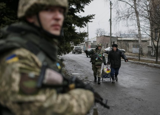 A member of the Ukrainian armed forces assists a local resident onto a bus to flee the military conflict, in Debaltseve, eastern Ukraine, February 6, 2015. (Photo by Gleb Garanich/Reuters)