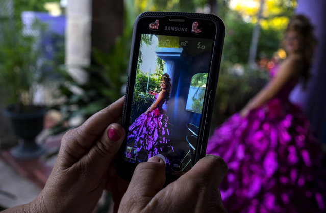 In this December 13, 2015 photo, Barbara Concepcion takes pictures of her daughter Amanda Teresa Betancur, who lives in Cuba, before her quinceanera party in Havana, Cuba. In the past, quinceanera photos typically featured girls in poufy dresses and crowns. But at many Havana studios, there are now punk-rock style sneakers and miniskirts among the rows of high heels and gowns. (Photo by Ramon Espinosa/AP Photo)