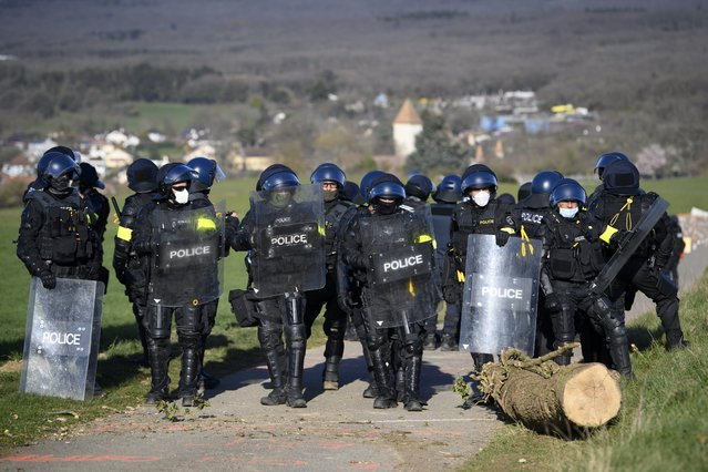 """Swiss police officers start the operation of the eviction of environmental protesters from the ZAD de la Colline """"Zone A Defendre"""" (zone to defend) installed by environmental activists in the the so-called """"plateau de la Birette"""" to block the extension of the Mormont quarry operated by the cement company LafargeHolcim between Eclepens and La Sarraz, Switzerland, Tuesday, March 30, 2021. (Photo by Jean-Christophe Bott/Keystone)"""