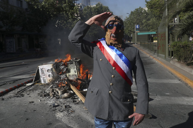 In this November 6, 2019 file photo, an anti-government demonstrator costumed as late military dictator Gen. Augusto Pinochet salutes in front of a burning street barricade placed by protesters demanding a new constitution in Santiago, Chile. Chileans will elect an assembly on April 11, 2021, tasked with writing fresh governing principles and putting them to a national vote in the first half of 2022 to replace the much-amended relic of military rule, the 1980 constitution. (Photo by Esteban Felix/AP Photo/File)