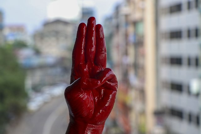 An anti-coup protester shows the three fingered salute of resistance on his red painted hand in memory of protesters who lost their lives during previous demonstrations in Yangon, Myanmar on Tuesday, April 6, 2021. Threats of lethal violence and arrests of protesters have failed to suppress daily demonstrations across Myanmar demanding the military step down and reinstate the democratically elected government. (Photo by AP Photo/Stringer)
