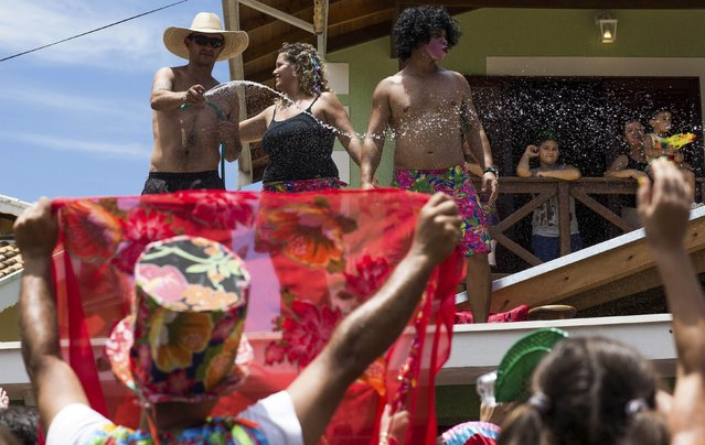 """Residents splash water on revellers taking part in an annual carnival block party known as """"Juca Teles"""" in Sao Luiz do Paraitinga February 14, 2015. (Photo by Roosevelt Cassio/Reuters)"""