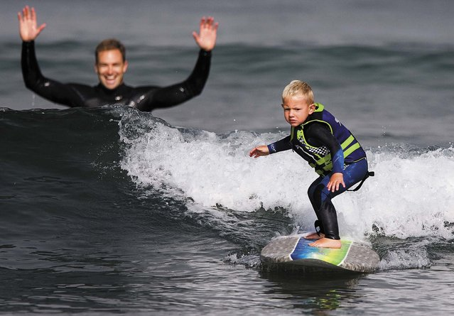"Triston surfs a wave as his father, Todd, watches in Morro Bay. ""Hes the most coordinated 3-year-old I've ever seen"", says the 35-year-old captain/paramedic with the Morro Bay Fire Department. (Photo by Joe Johnston/The Tribune of San Luis Obispo)"