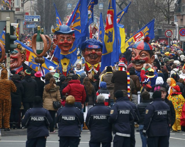 Police stand guard next to revellers during the traditional Rose Monday carnival parade in Mainz February 16, 2015. (Photo by Ralph Orlowski/Reuters)