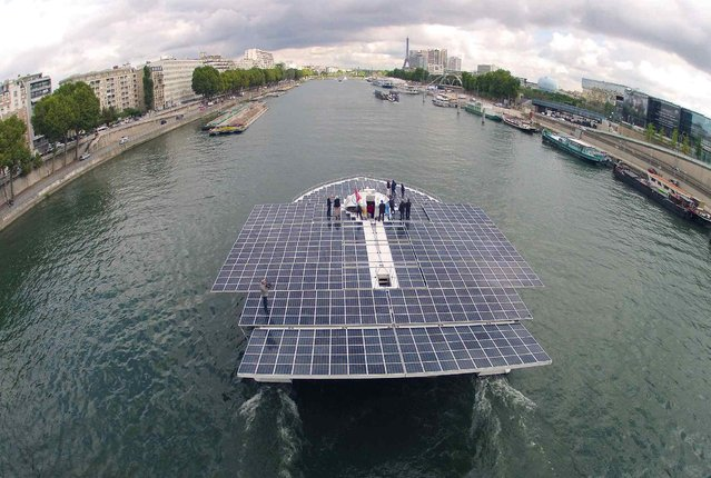 The Turanor PlanetSolar, the world's largest solar-powered boat, travels on the Seine river next to the Eiffel tower in Paris September 10, 2013. PlanetSolar, a catamaran powered exclusively by solar energy, completed the first solar-powered trip around the world on May 4, 2012 after travelling over 60,000 km (37,282 miles) in 584 days. (Photo by Charles Platiau/Reuters)