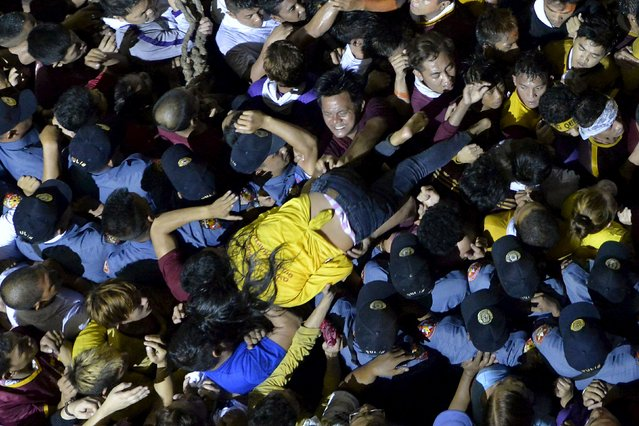 A woman crawls on the shoulders of fellow devotees and policemen as the carriage bearing the image of the Black Nazarene arrives at Quiapo church after more than 20 hours annual procession in Manila, January 10, 2016. (Photo by Ezra Acayan/Reuters)