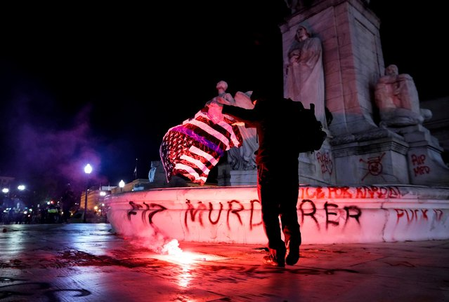 A fire is seen as a protester holds a thin blue line flag at the Christopher Columbus Memorial Fountain during a demonstration in Washington, D.C. to protest police violence, after the death of Daunte Wright, who was shot and killed by a police officer in Minnesota, U.S., April 17, 2021. (Photo by Erin Scott/Reuters)