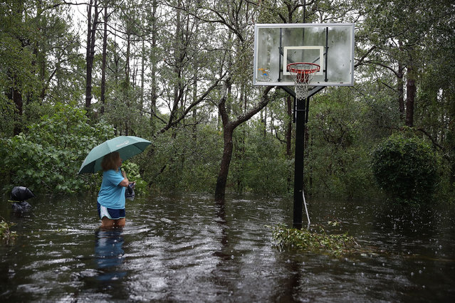 Kim Adams makes her way to her home that is surrounded by flood waters after Hurricane Florence passed through the area on September 15, 2018 in Southport, N.C. (Photo by Joe Raedle/Getty Images)