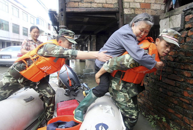 Paramilitary policemen carry an elderly woman off a raft as they rescue trapped residents after Typhoon Fitow hit Taizhou, Zhejiang province October 8, 2013. Four people were killed and hundreds of thousands evacuated after Typhoon Fitow hit eastern China, destroying houses and farmlands and closing ports and airports. (Photo by Reuters/China Daily)