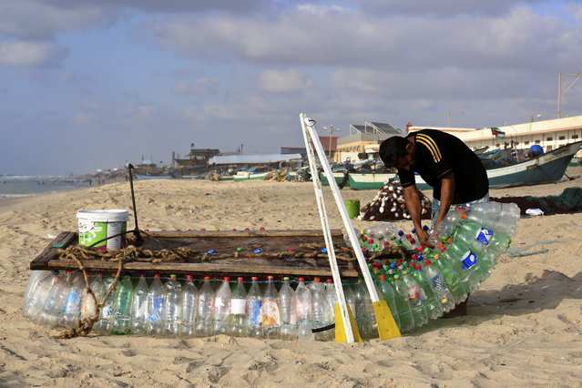 Palestinian fisherman Mouad Abu Zeid repairs his boat that he made of 700 Plastic empty bottles on a beach in Rafah in the southern Gaza Strip on August 14, 2018. Zeid used 700 empty bottles and thread from damaged fishing nets to make the boat which cannot sail too far but far enough to catch about seven or eight kilos of various kinds of fish per day using rods. Israel on August 15 returned the fishing zone it enforces off the strip to nine nautical miles in the south of the enclave. The limit is six nautical miles in the north, which borders Israel. (Photo by Said Khatib/AFP Photo)