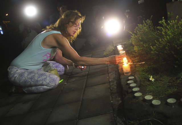 A woman lights a candle before praying in front of Kerobokan prison, before the transfer of the two Australian death row prisoners, Myuran Sukumaran and Andrew Chan, to the airport in Denpasar, on the Indonesian island of Bali March 4, 2015. REUTERS/Zul Edoardo