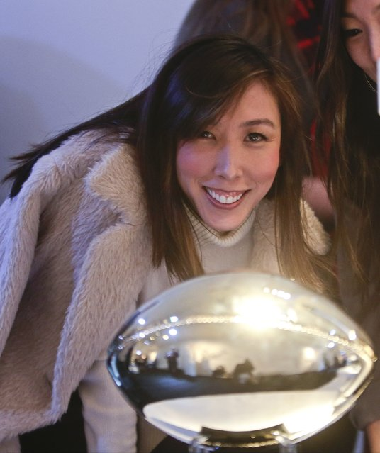 Jewelry designer Cynthia Sakai stands near a football she designed for Vita Fede, at the unveiling of the CFDA footballs Wednesday, January 20, 2016, at the NFL headquarters in New York. (Photo by Frank Franklin II/AP Photo)