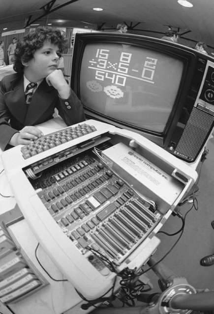 Jeff Leff, 9, Toronto, Canada, visiting show with parents at Boston Computer show, August 25, 1977, tries math problems via TV set and computer meant for home use by Apple Computer, Inc. (Photo by AP Photo/CM)