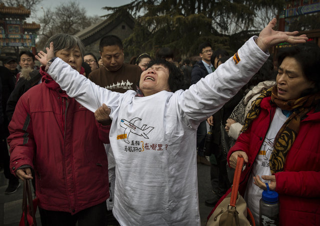 Chinese relative of a missing passenger on Malaysia Airlines flight MH370 reacts as she weeps outside the main gate of the Lama Temple on March 8, 2015 in Beijing, China. Foreign and local media were prevented by Chinese police from covering the relatives visit to the temple where they tried to pray .There were 239 people on board the flight when it disappeared March 8, 2014 en route from Kuala Lumpur to Beijing. After one year and an exhaustive search, investigators still have no clue as to the whereabouts of the missing airliner.  (Kevin Frayer/Getty Images)