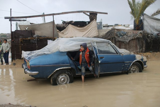 A Palestinian boy gets out of his father's car amidst flood waters during a winter storm in Khan Younis in the southern Gaza Strip January 25, 2016. (Photo by Ibraheem Abu Mustafa/Reuters)