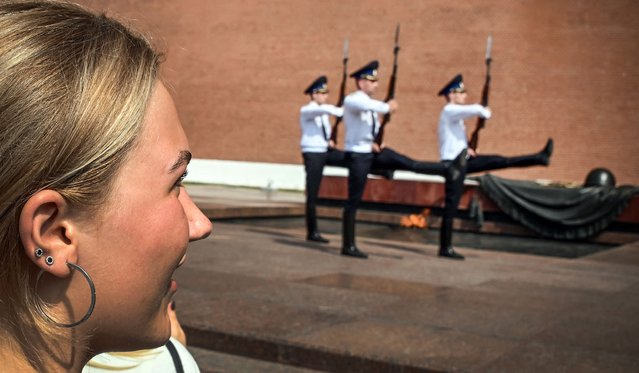 A woman looks at the honour guard soldiers marching at the Tomb of the Unknown Soldier by the Kremlin wall, in downtown Moscow, on June 28, 2021. (Photo by Alexander Nemenov/AFP Photo)