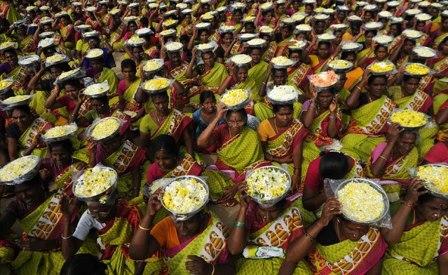 Indian women carry plates of flower for an offering during a ceremony for the victims of the 2004 tsunami at Marina Beach in Chennai on December 26, 2016. The earthquake and tsunami that struck the Indian Ocean on December 26, 2004 killed over 230,000 people and devastated coastal communities, including the shorelines of the southern Indian states of Tamil Nadu, Andhra Pradesh, and Kerala. (Photo by Arun Sankar/AFP Photo)