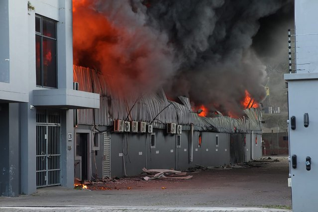 A factory burns on the outskirts of Durban, South Africa, Wednesday, July 14, 2021 in ongoing unrest. Rioting has continued which was sparked by the imprisonment last week of ex-President Jacob Zuma resulting in days of looting in two of the country's nine provinces. (Photo by AP Photo/Stringer)