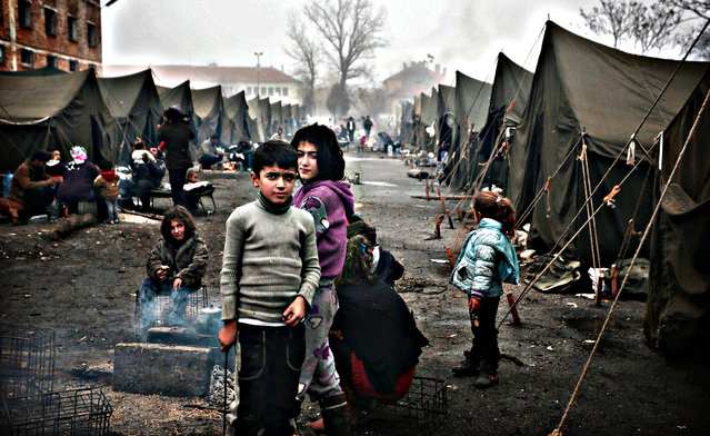 Syrian children try to stay warm near an open fire in front of their unheated tents in a refugee camp in the town of Harmanli, Bulgaria, Thursday, November 21, 2013. Thousands of Syrian and other refugees from the Middle East, Asia and Africa, who find enough courage to make a dangerous journey from their war-ravaged states, often end up in the crammed settlements in the Balkans, including Bulgaria, Greece or Serbia, after being caught on the borders of wealthy Western European nations for attempting to cross illegally. (Photo by Valentina Petrova/AP Photo)