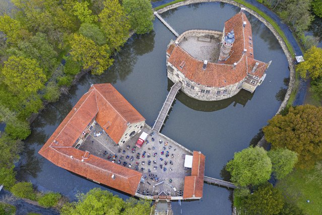 In this aerial view taken with a drone, around 100 spectators are seated during a concert as part of the Coesfeld model region at Burg Vischering, in L'dinghausen, Germany, Saturday, May 8, 2021. The circle presents the guitar virtuosos M. and T. Hoene. Admission was from 17:30 only with a negative coronavirus test. (Photo by Guido Kirchner/dpa via AP Photo)