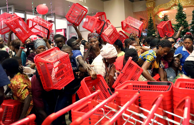 People reached out to pick baskets at a newly commissioned Shoprite store at Novare Gateway mall Abuja, Nigeria November 30, 2017. (Photo by Afolabi Sotunde/Reuters)