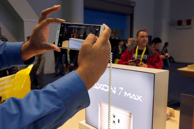 A man takes a photo with an Axon 7 Max smartphone with 3D camera at the ZTE booth during the 2017 CES in Las Vegas, Nevada January 6, 2017. (Photo by Steve Marcus/Reuters)