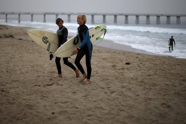 Kevin Elliott, 12, (L) and Carlos Price Gracida, 13, walk up the beach after surfing before school at sunrise in Hermosa Beach, California March 31, 2015. (Photo by Lucy Nicholson/Reuters)
