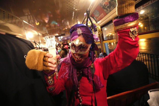 """Cheryl Gerber, a member of the """"Societe des Champs Elysee"""" rides the Rampart-St. Claude street car line, which just opened last fall, to commemorate the official start of Mardi Gras season, in New Orleans, Friday, January 6, 2017. Wearing masks and festive costumes, they honored their king and queen at a neighborhood bar and danced as a brass band played """"Carnival Time"""", before boarding their red street car. (Photo by Gerald Herbert/AP Photo)"""