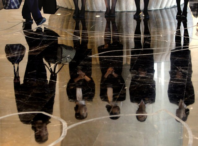 A porter carries luggage past a group of reception staff that are reflected in the floor as they stand in the foyer of the five-star rated Sofitel Hotel in Beijing in this November 19, 2007 file photo. (Photo by David Gray/Reuters)
