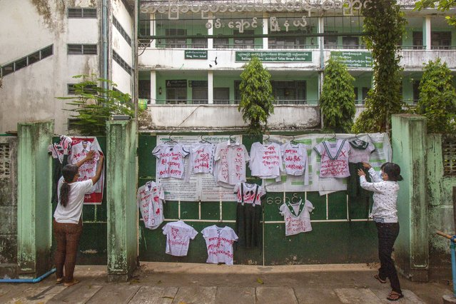 Activists and anti-coup protesters hang student uniforms on the wall of a school during a demonstration against the re-opening of the school by the government in Yangon, Myanmar, Tuesday, April 27, 2021. Demonstrations have continued in many parts of the country since Saturday's meeting of leaders from the Association of Southeast Asian Nations, as have arrests and beatings by security forces despite an apparent agreement by junta leader Senior Gen. Min Aung Hlaing to end the violence. (Photo by AP Photo/Stringer)