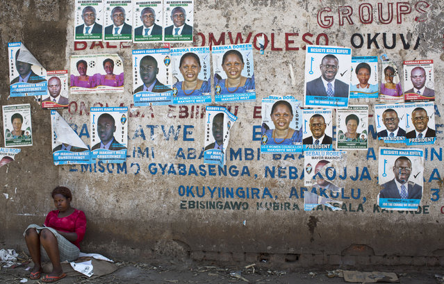 A woman sits against a wall plastered with campaign posters for opposition leader Kizza Besigye, as well as for local members of Parliament, in a poor market area of the capital Kampala, Uganda Wednesday, February 17, 2016. (Photo by Ben Curtis/AP Photo)