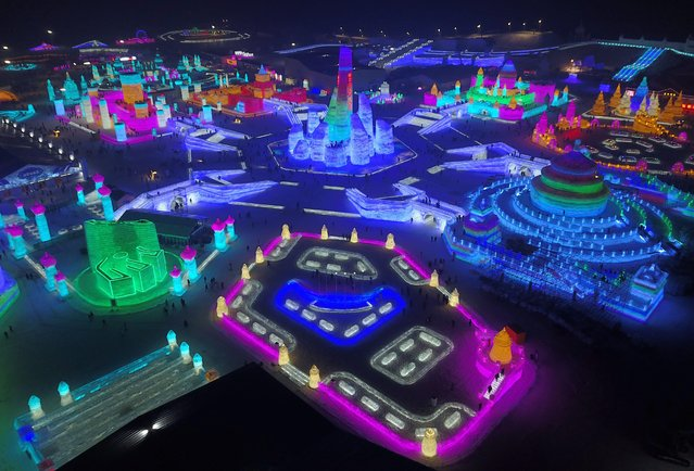 An aerial view shows people touring between the large-scale ice sculptures at the 18th Harbin Ice and Snow World during its trial run opening to public in Harbin city, Heilongjiang province, China, 21 December 2016. Some 180,000 cubic meters of ice and 150,000 cubic meters of snow were used to build the 800,000-square-meter ice wonderland. The 33rd Harbin International Ice and Snow Festival will kick off on 05 January 2017 that will last about three months. (Photo by Tian Weitao/EPA)