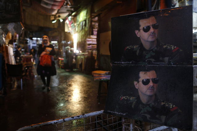 Pictures of the Syrian President Bashar Assad are seen at a check point on one of the entrances to the popular Hamidiyeh old market in Damascus , Syria, Sunday, February 21, 2016. The Islamic State group claimed responsibility for a triple blast in Sayyida Zeinab, a Shiite suburb of Damascus,  saying two IS fighters set off a car bomb before detonating their explosive belts, killing dozens. (Photo by Hassan Ammar/AP Photo)