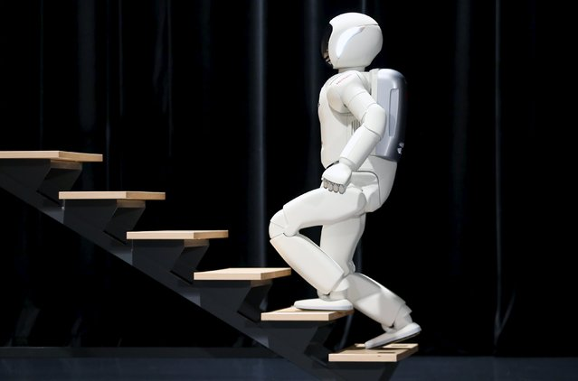 Honda's latest version of the Asimo humanoid robot walks up stairs during a presentation in Zaventem near Brussels in this July 16, 2014 file photo. (Photo by Francois Lenoir/Reuters)