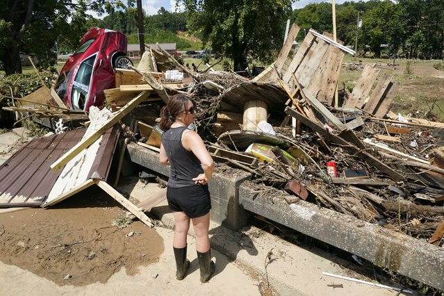 A woman looks at debris washed up against a bridge over a stream Sunday, August 22, 2021, in Waverly, Tenn. (Photo by Mark Humphrey/AP Photo)